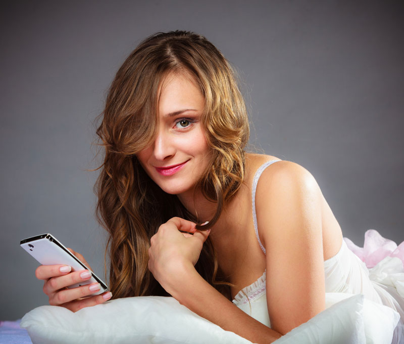 Attractive woman smiling and flirting with phone in her hand